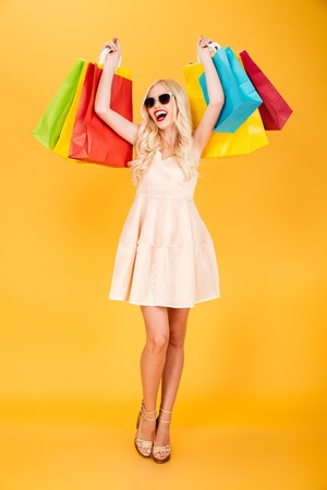 Image of happy young blonde woman standing isolated over yellow wall background. Looking aside holding shopping bags. Stok Fotoğraf