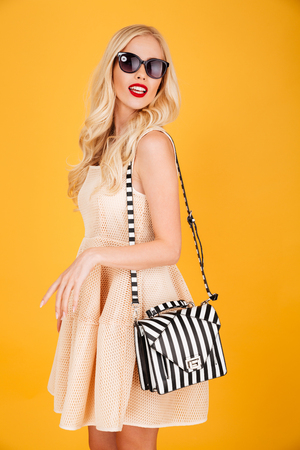 Picture of amazing young fashion blonde woman posing isolated over yellow wall background. Looking aside wearing sunglasses.