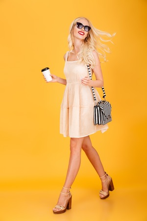 Image of amazing young fashion blonde woman walking isolated over yellow wall background. Looking aside wearing sunglasses drinking coffee.