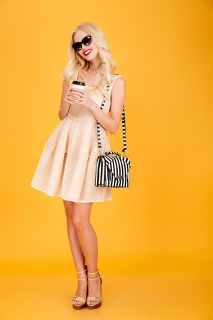 Picture of amazing young fashion blonde woman posing isolated over yellow wall background. Looking camera wearing sunglasses drinking coffee.