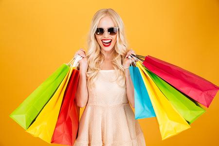 젊은 금발의여자가 서있는 노란 벽 배경 위에 절연 서 웃는의 그림. 카메라를 찾고 쇼핑 가방을 찾고.