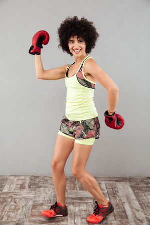 Full length image of happy sports woman posing with boxing gloves and looking at the camera over gray background
