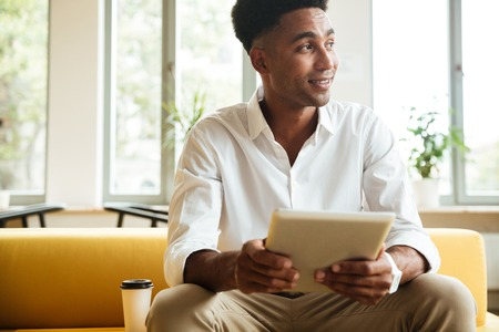 Image of cheerful young african man sitting coworking by tablet computer. Looking aside.
