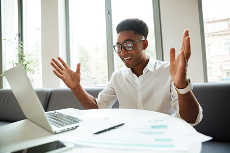 Photo of cheerful young african man sitting coworking by laptop computer. Looking aside. Stock Photo