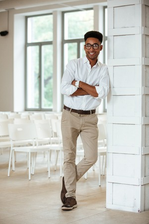 Picture of cheerful young handsome african man standing in office. Looking camera.