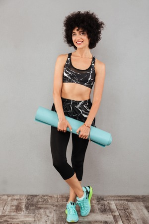 Full length picture of pleased sports woman holding fitness mat and looking at the camera over gray background