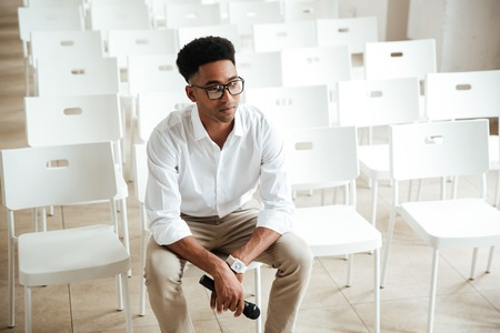 Image of young concentrated african man sitting in office indoors holding microphone. Looking aside. Stock Photo