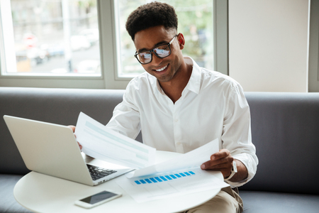 Picture of happy young african man sitting coworking by laptop computer holding documents. Looking aside. Stock Photo