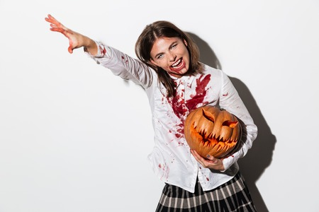 Smiling mad zombie woman covered in blood stains holding a halloween pumpkin and pointing away isolated over white background Stock Photo