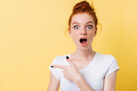 mujer sorprendida del jengibre en camiseta apuntando hacia arriba y mirando a la cámara sobre fondo amarillo Foto de archivo