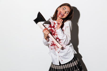 Happy smiling zombie woman holding an axe and looking at camera isolated over white background Stock Photo
