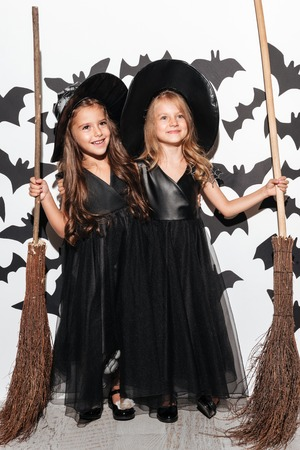 Couple of two funny little girls dressed in halloween costumes holding brooms and posing with bats on a background