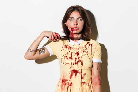Wütende gruselige Zombiefrau, die ihre Kehle mit einem Messer schneidet und die Kamera lokalisiert über weißem Hintergrund betrachtet