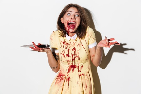 Happy mad zombie woman holding a knife and laughing isolated over white background