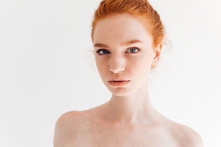 Close up portrait of beauty naked ginger woman looking at the camera over white background