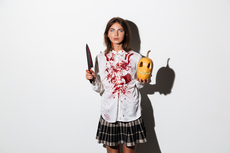 Bruised and bloody zombie woman holding large knife and carved pumpkin isolated over white background