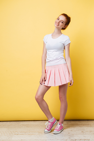 Full length image of attractive ginger girl in t-shirt and skirt looking at the camera over yellow background