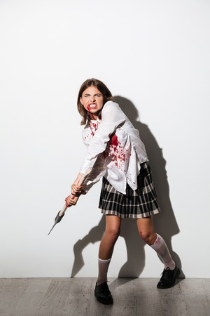 Full length of a mad zombie woman holding an axe and ready to attack isolated over white background