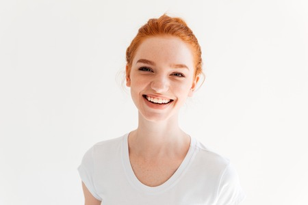 Close up picture of happy ginger woman in t-shirt looking at the camera over white background