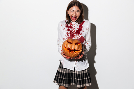 Happy smiling zombie woman covered in blood stains holding a halloween pumpkin isolated over white background Stock Photo