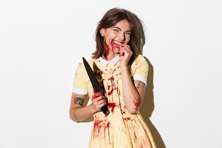 Bruised and blood stained zombie woman holding a knife and laughing isolated over white background Stock Photo