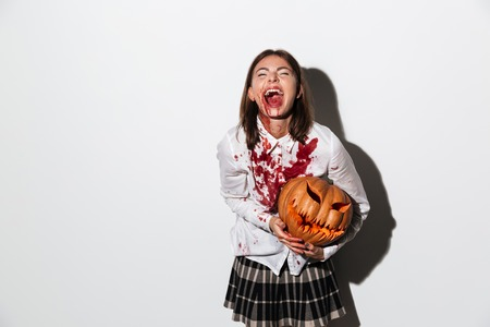 Crazy dreadful zombie woman covered in blood stains holding a halloween pumpkin and laughing isolated over white background