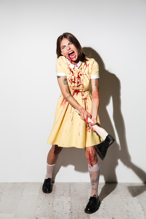 Full length of a scary zombie girl covered with blood stains ready to attack with a large axe isolated over white background