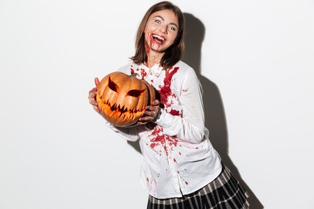 Happy zombie woman covered in blood stains holding a halloween pumpkin and laughing isolated over white background