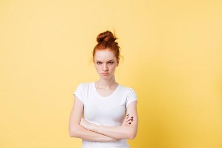 Het boze gembervrouw stellen met gekruiste wapens en het bekijken de camera over gele achtergrond Stockfoto