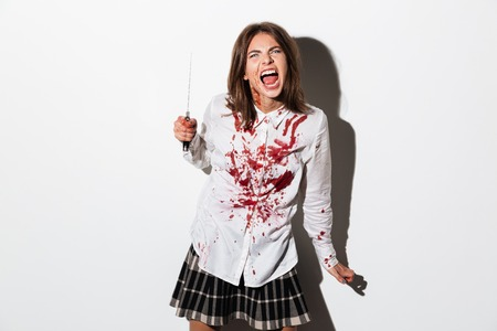 Zombie woman with wounds and blood stains holding a large knife and ready to attack isolated over white background