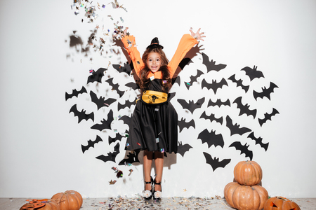 Cute little girl dressed in halloween costume having fun with bats and falling confetti on a background