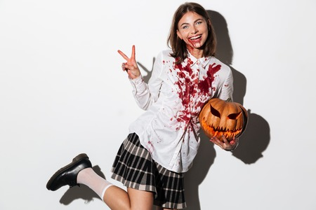 Smiling zombie woman covered in blood stains holding a halloween pumpkin and laughing isolated over white background Stock Photo