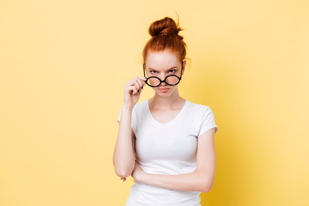 Angry ginger woman looking through eyeglasses at the camera over yellow background