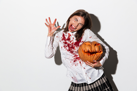 Mad dreadful zombie woman covered in blood stains holding a halloween pumpkin isolated over white background