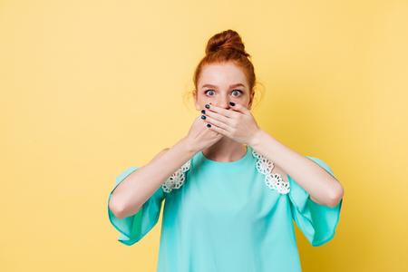 Verraste gembervrouw die haar mond behandelt en de camera over gele achtergrond bekijkt