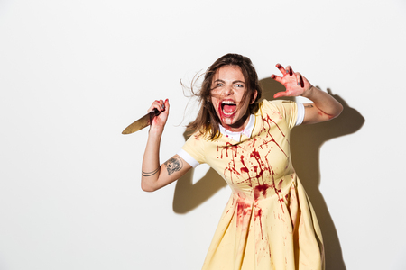 Mad woman in blood splattered dress ready to attack with a knife isolated over white background