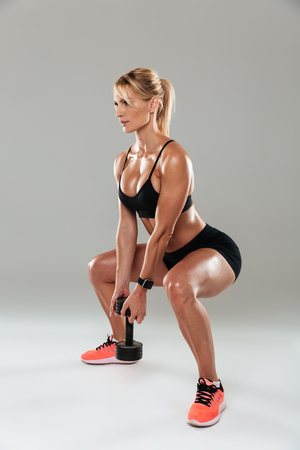 Full length side view of a athlete woman doing squats with a dumbbell isolated over gray background