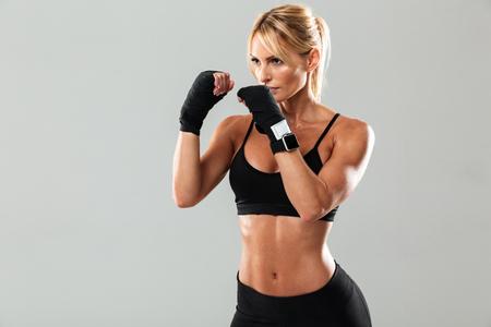 灰色の背景の上に孤立した若い筋肉のスポーツウーマンボクシングの肖像