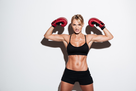 Portrait of a strong young athlete woman flexing muscles in boxing gloves isolated over white background