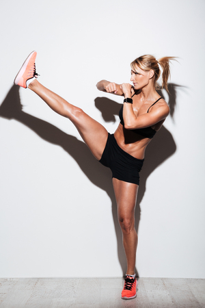 Full length portrait of young focused sportswoman doing kickboxing exercises isolated over white background