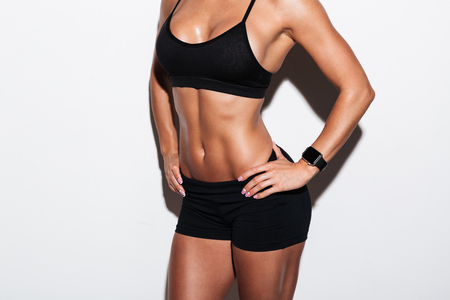 Cropped image of a muscular young woman in sportswear standing isolated over white background