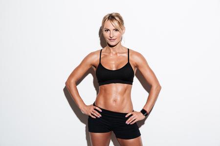 흰색 배경 위에 절연 엉덩이에 손으로 서있는 동안 포즈 꽤 운동 선수 여자 웃고 스톡 콘텐츠