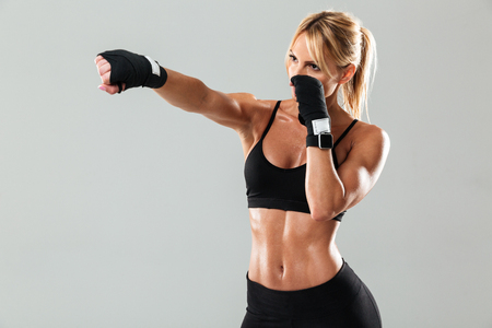 Portrait of a blonde muscular sportswoman doing boxing exercices isolated over gray background
