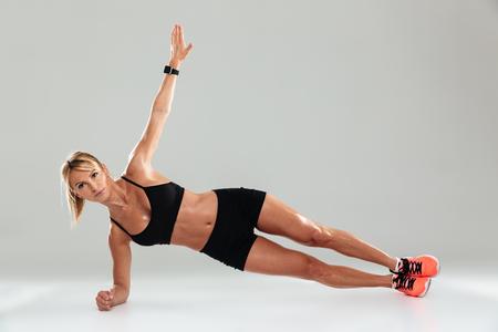 Junge gesunde Sportlerin, die Planking tut und die Kamera lokalisiert über grauem Hintergrund betrachtet Standard-Bild - 87772752