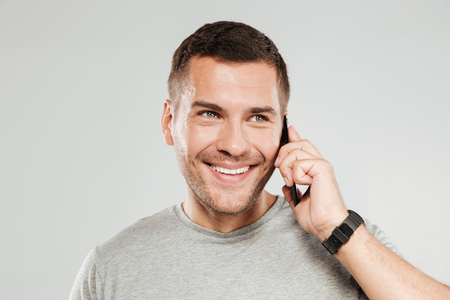 Image of young happy man dressed in grey t-shirt isolated over grey wall background. Looking aside while talking by mobile phone.