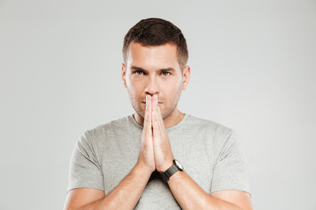 Image of young serious man dressed in grey t-shirt isolated over grey wall. Looking camera and prays. Stok Fotoğraf