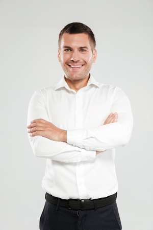 Image of happy young man dressed in white shirt isolated over grey wall background. Looking at camera with arms crossed.