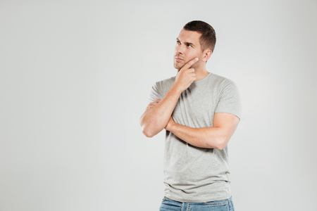 Image of concentrated thinking young man dressed in grey t-shirt isolated over grey wall background. Looking aside.