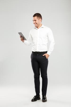회색 벽 배경 위에 고립 된 흰 셔츠를 입고 웃는 젊은이의 이미지. 태블릿 컴퓨터 옆에 채팅을 찾고. 스톡 콘텐츠
