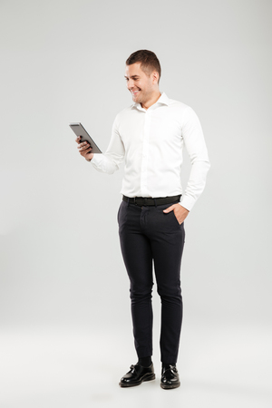Image of smiling young man dressed in white shirt isolated over grey wall background. Looking aside chatting by tablet computer.